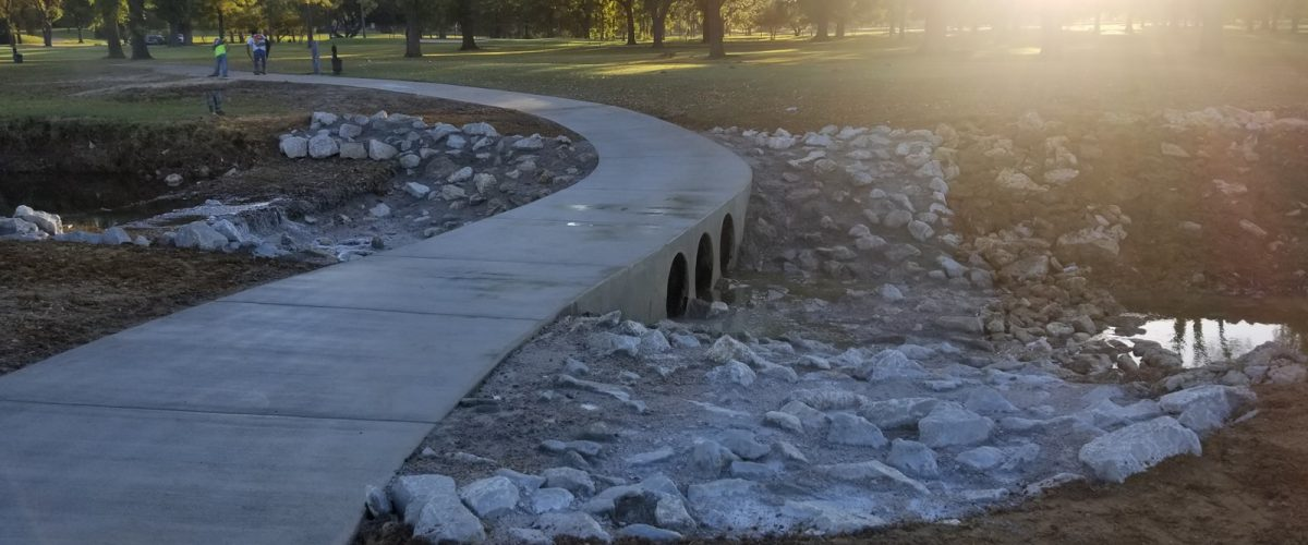 Creek with concrete and stone sidewalk over it